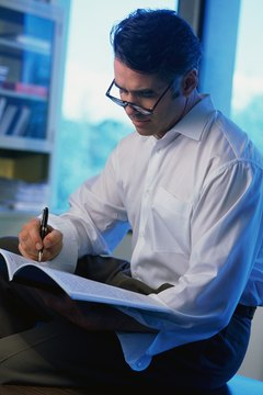 Man editing document, sitting on desk