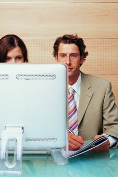Businesswoman Sitting Behind a Computer Monitor Sitting by a Businessman Writing in a Notepad With a Ballpoint Pen