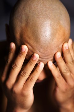 portrait of a young african american man as he buries his head in his hands