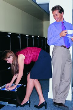 Businessman With a Coffee Looking Down at a Young Businesswoman Bending Over and Filing Documents in a Filing Cabinet