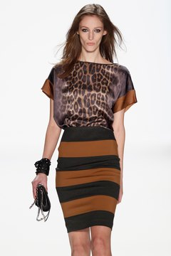 A model tucks a loose silk blouse into her bodycon skirt in the Laurel show during Mercedes Benz Fashion Week.