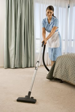 Maid vacuuming carpet