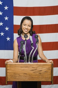 Woman speaking at podium with microphones in front of an American flag