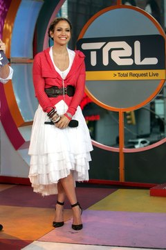 "Jennifer Lopez wears a white skirt, red sweater and black pumps for an appearance on MTV's ""Total Request Live."""