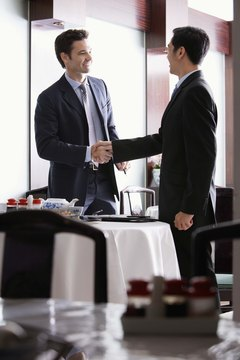 Businessmen shaking hands in restaurant