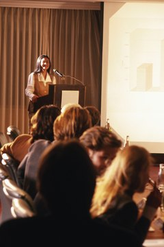 Woman giving presentation to group of business people
