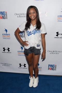 Olympic gymnast Gabby Douglas goes for a sporty look by pairing her white Jordans with a baseball jersey.