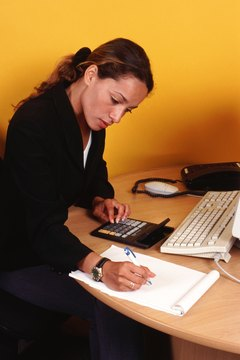 Businesswoman sitting at desk using calculator