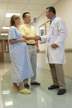 husband and pregnant wife in hospital with doctor - Endocrinologist Job Description