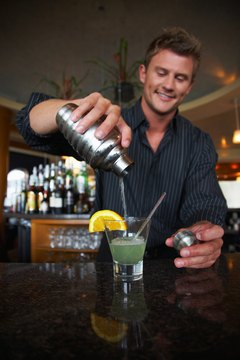 Bartender pouring alcoholic beverage in glass