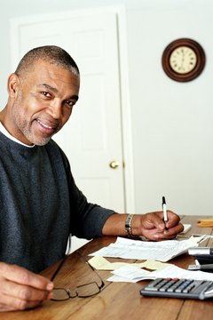 Mature man doing finances in home office, portrait
