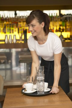 Young waitress clearing table in bar, smiling