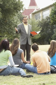 Male lecturer teaching  students on a lawn