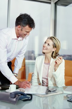 Businesswoman sitting at desk smiling at male colleague