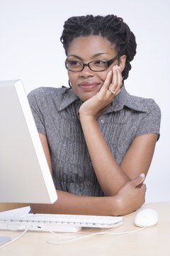 Young woman sitting at desk using computer, smiling