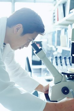 Research scientist looking into microscope, side view