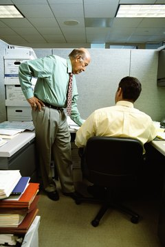 Businessmen in office cubicle, having meeting