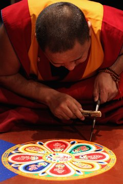 A Buddhist monk creates a sand mandala, symbolizing the impermanent universe.