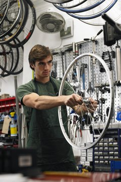 Young man holding wheel of bicycle in shop