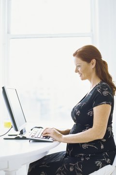 side profile of a pregnant woman working on a computer