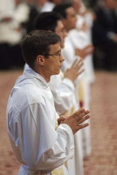Catholic deacons, shown here praying in Vatican City, are servants of the bishop.