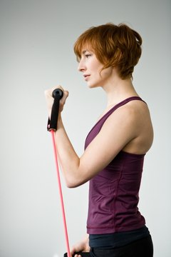 Biceps curls are performed while standing on one end of the tubing.