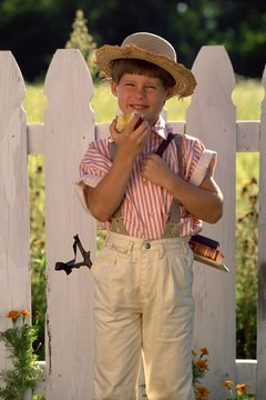 Boy in front of white picket fence