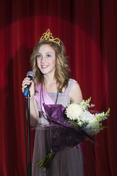 A king and queen pageant will typically award the winner with a crown, sash and a bouquet of flowers.