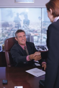 portrait of a businessman sitting at his desk shaking hands with a woman standing across
