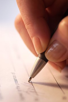 Extreme close-up of woman's hand as she signs her name to a document.