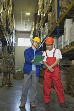Workers Looking At Clipboard In Warehouse