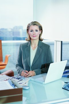 Portrait of a Mature CEO Sitting at Her Desk Holding a Ballpoint Pen