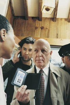 Mature Special Agent With Colleagues in a House Showing His ID Card to a Woman