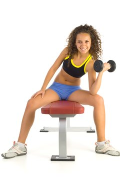 Exercise your chest with dumbbells and a weight bench.