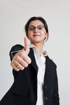 Businesswoman making thumbs up gesture, smiling, portrait