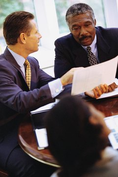 Two men talking together in meeting, one pointing to paper