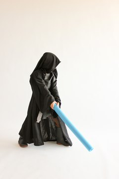 Child wearing a black Star Wars, Dark Side Annakin costume with brown robe.