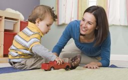 Una buena maestra de guardería no tienen miedo de sentarse en el piso y jugar con los niños.