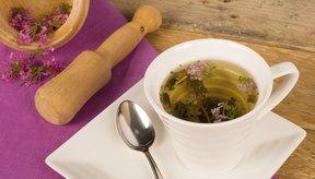 Las flores de valeriana en un bol de madera junto a una taza de té de valeriana caliente.