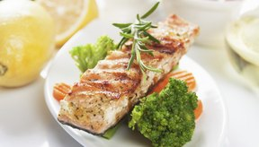 Salmón grillé en un plato con brócoli y zanahorias.