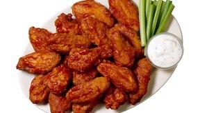 Sirve las alas de pollo con salsa ranchera baja en grasas y apio.