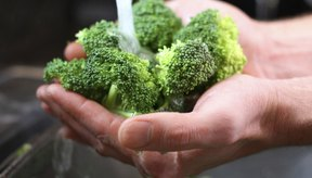Hombre lavando un puñado de brócoli.