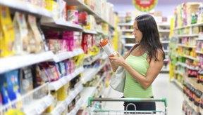 Mujer leyendo la etiqueta de alimentos en el supermercado.