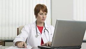 Doctor que mira la computadora portátil.
