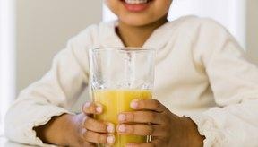 Niña pequeña bebe un vaso de jugo de naranja.