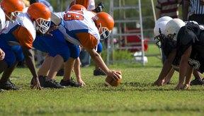Dos equipos de fútbol americano juvenil se alinean para jugar.