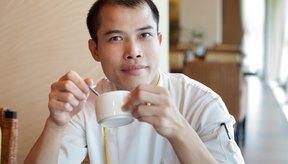 Hombre calvo que sostiene una taza de café.