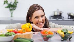 Una mujer sonriendo detrás de pimientos.