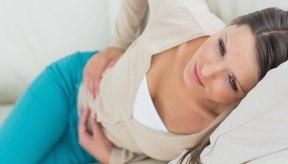 Una mujer se encuentra incómoda en el sofá mientras sostiene su bajo vientre.