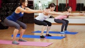Tres mujeres realizando sentadillas en el gimnasio.